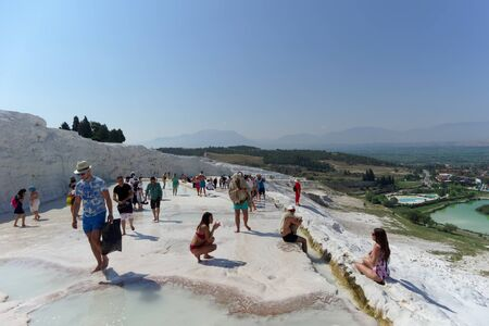 Denizli, Turkey. - July 20.2019. Tourists walk on a snow-white terraces at Pamukkale in Turkey. Editoriali
