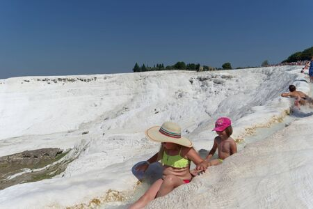 Denizli, Turkey. - July 20.2019. View of the snow-white Pamukkale in Turkey Children sit in a ditch with running water.