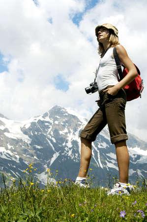 vrouw in de bergen en zien op hoge piek Stockfoto
