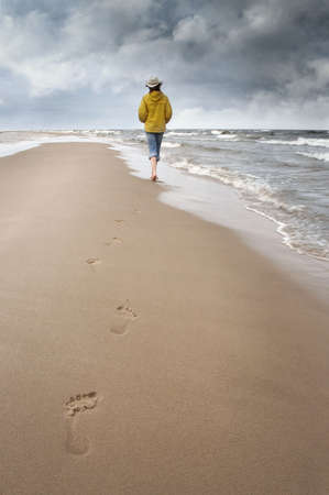 woman walks along coast and see on storm clouds
