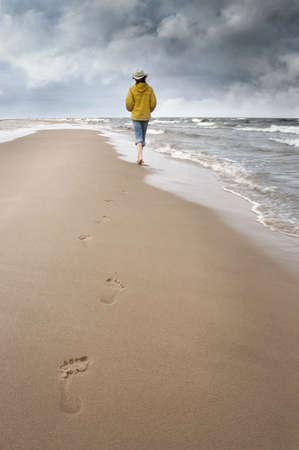 vrouw loopt langs de kust en zien op onweerswolken