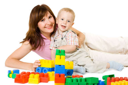 Mother and little son playing with bright block. White isolated.