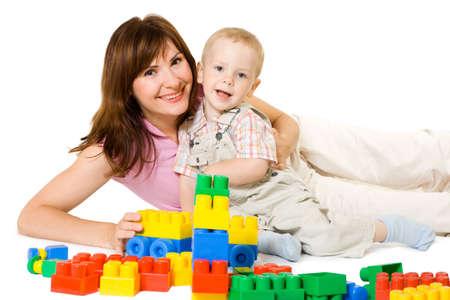 Moeder en zoontje spelen met lichte blok. White geïsoleerd.