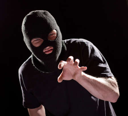 aggressive burglar in black mask, robbing and catching something by hand Foto de archivo
