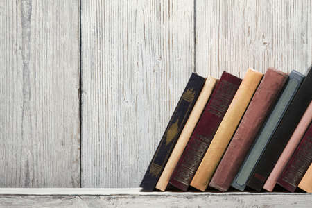 old book shelf blank spines, empty binding stand on wood texture background, knowledge concept