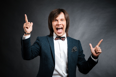 finger bow: smiling handsome man with long hair brunette and brown eyes in dark suit with stripes and bow tie  looking forward and showing two finger sign at black background