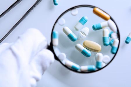 farmaci sospetti sotto una lente d'ingrandimento Archivio Fotografico