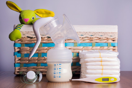 breast pump, thermometers, diapers and a baby's nipple in the background of a wicker basket with a toy Standard-Bild