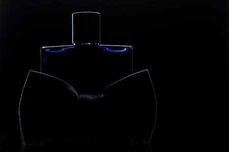 bottle of perfume bowtie on black