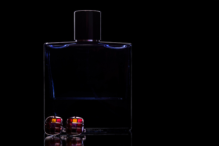 A bottle of perfume and cufflinks on black