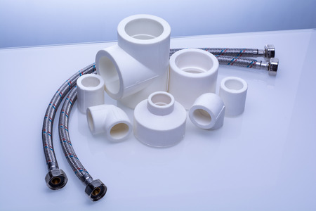 set of fittings for PVC pipes and reinforced water hose on a white background