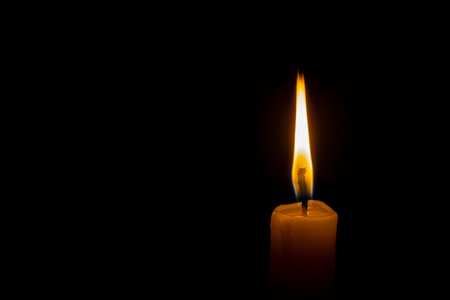 a lonely burning candle in the darkness