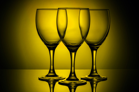 three empty glasses on a yellow background