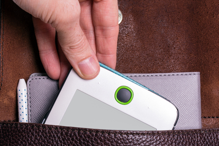 a mans hand puts an e-book in a backpack