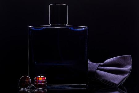 une bouteille de parfum et des boutons de manchette et un nœud papillon sur un fond noir