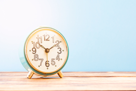 Turquoise retro alarm clock on a wooden table with sun rays 스톡 콘텐츠