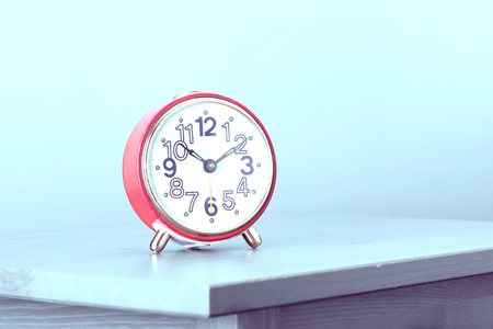 red retro alarm clock on the bedside table 스톡 콘텐츠