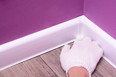 technology of installation of a white floor plinth. home improvement concept Stock Photo