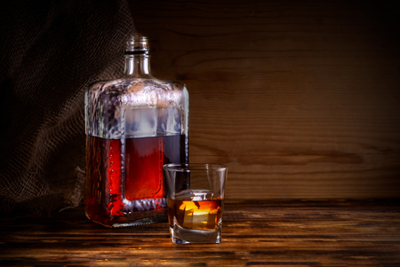 glass with alcohol drink and bottle on wooden background