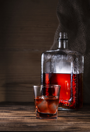 glass of whiskey with bottle on wooden background Imagens