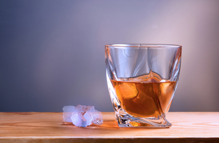 glass with drink and ice on wooden table