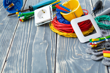 Tools for electrician and cables on gray wooden surface Imagens