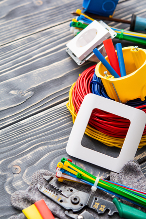 Tools for electrician and cables on gray wooden surface