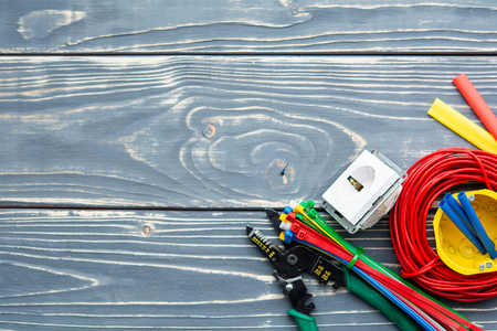Different electrician's supplies on gray wooden background.