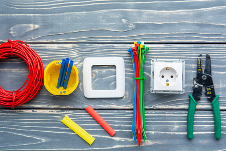 Electricians supplies on gray wooden background