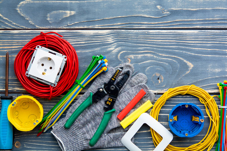 Electrician's supplies on gray wooden background Фото со стока
