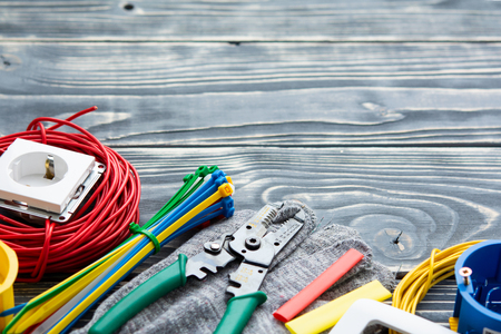Professional electrician set on gray wooden background Imagens