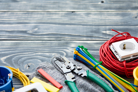 Different electricians supplies on gray wooden background. Imagens