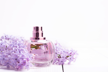 pink bottle of women's perfume with lilac flowers on white wooden background
