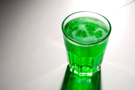 glass with green soda on a white background