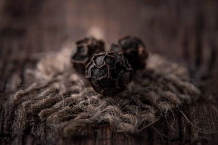 grains of black pepper on jute fabric close-up Stock Photo