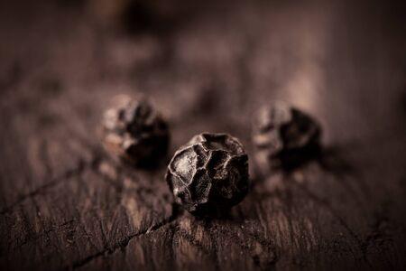 black pepper grains on wooden background close-up