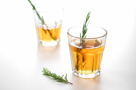 alcoholic drink with lemon and rosemary on a white background