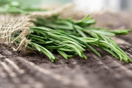 freshly cut rosemary leaves on a brown wooden surface