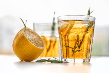 glasses of soda with lemon and rosemary on a light background 免版税图像