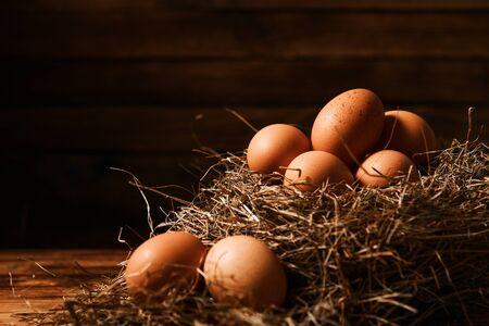 Jaja kurze w wiklinowych gniazdach w widoku z góry kurnika. Naturalne ekologiczne jaja w sianie. Świeże jaja kurze.