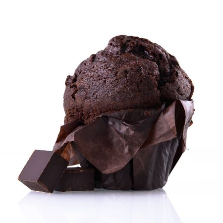 Chocolate muffin in brown paper with pieces of dark chocolate on a white isolated background. Chocolate cake on a white mirror surface.
