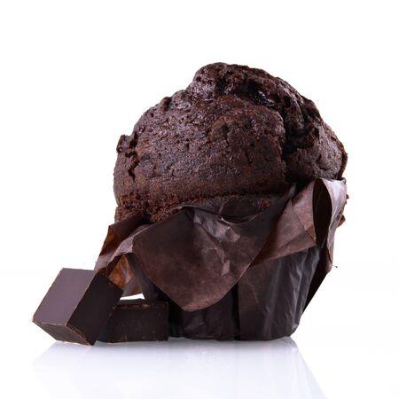 Schokoladenmuffin in braunem Papier mit Stücken dunkler Schokolade auf weißem, isoliertem Hintergrund. Schokoladenkuchen auf einer weißen Spiegeloberfläche.