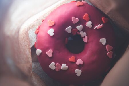 Pink donut with hearts in a paper bag, close-up. top view Stockfoto