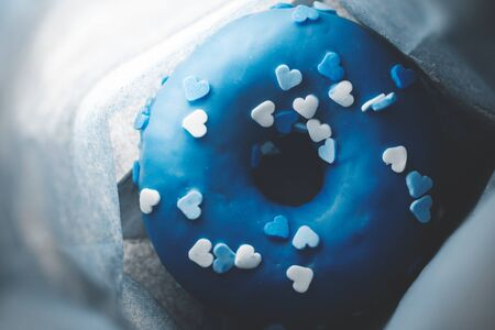 Blue donut with hearts in a paper bag, close-up. top view