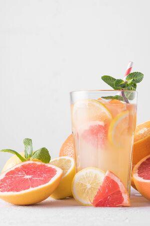 Letnia orzeźwiająca lemoniada z miętą na jasnym tle. Kieliszek koktajlu cytrusowego w jasnym kluczu. Zbliżenie. Letni koktajl witaminowy z pomarańczy, cytryny i grejpfruta.