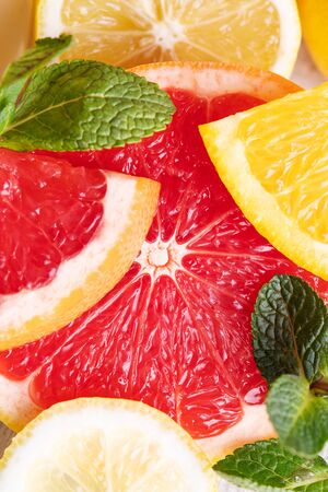 Citrus fruits with mint leaves close-up. Fresh slices of grapefruit, lemon and orange. top view.