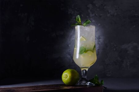 Refreshing lime cocktail with mint and ice on a dark background. Soft drink with lime and mint. Close-up Banque d'images