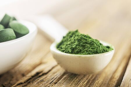 White spoon with chlorella or spirulina on an old wooden background. Stock Photo