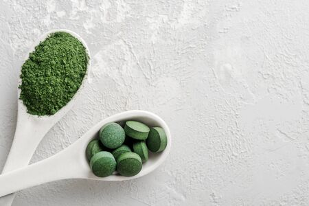 Two white spoons with chlorella or spirulina on a grey concrete background.