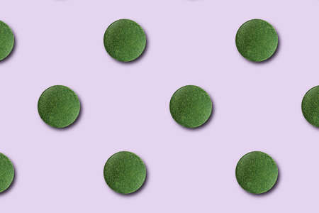 Seamless pattern of green chlorella or spirulina tablets on a pink background.